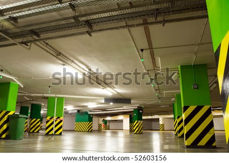 Parking lot, underground garage of shopping center. Neon light in bright industrial building.