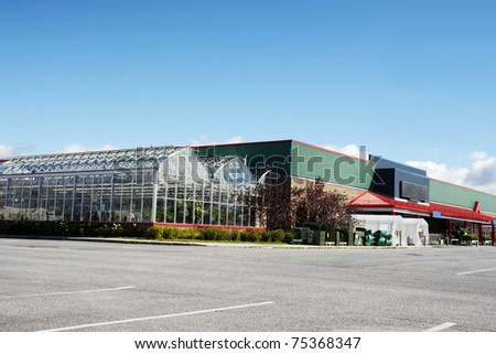 Parking lot view of a hardware store with greenhouse nursery attached to it