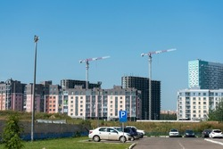 Parking of cars on the background of the city under construction. New city buildings and houses under construction with cranes. New residential areas of the city.