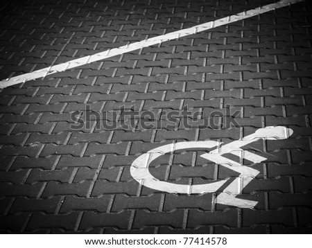 Parking place sign for disabled on grey dark brick