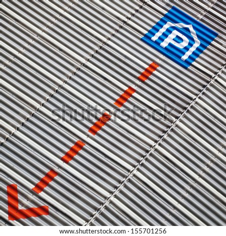 parking sign and an arrow at a corrugated sheet metal facade