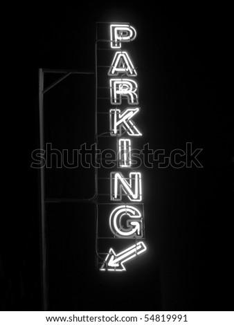 Parking sign neon light at night over dark sky