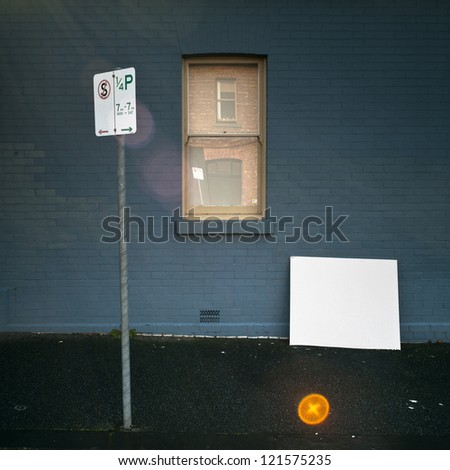 Parking sign on pavement with blank white board, blue wall and window. Surreal perspective and strong lens flare effect.