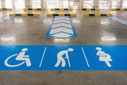 Parking space reserved for elderly people, disabled person, and pregnant women only, painted in blue and white on asphalt road with traffic dividing lines.