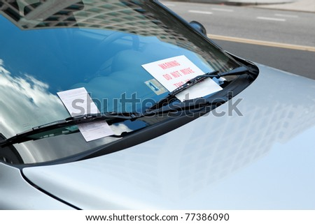 "Parking ticket placed under windshield wiper of a car.  There is also also warning sign that there is a ""boot"" attached to a wheel and the car cannot be driven until the fine is paid"