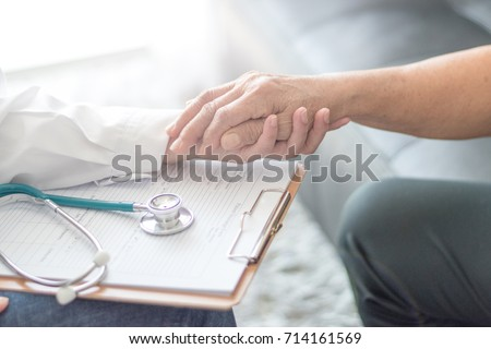 Parkinson and alzheimer female senior elderly patient with caregiver in hospice care. Old woman holding hand with doctor physician or Specialized Assistance.