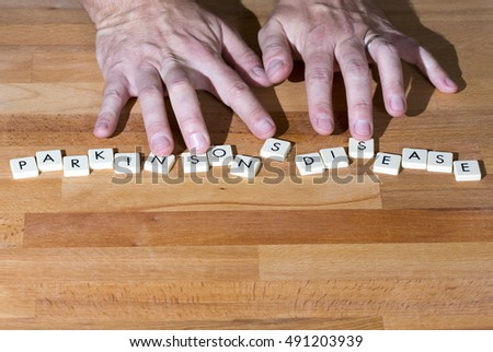 Parkinson's disease text on a wooden table. Shaking fingers touches the letters.