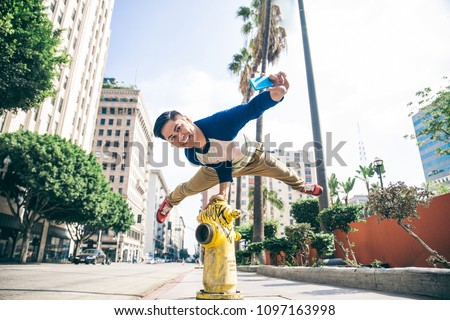 Parkour man doing tricks on the street - Free runner training his acrobatic port outdoors and taking a picture