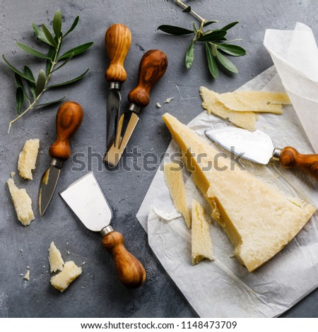 Parmesan cheese and knife on concrete background