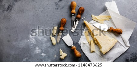 Parmesan cheese and knife on concrete background copy space
