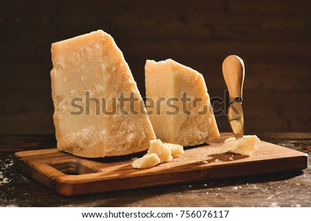 Parmesan cheese composition, on a wooden cutting board. One hand takes the knife and breaks a couple of pieces to savor the quality. Concept of: italy, cheese and tradition.
