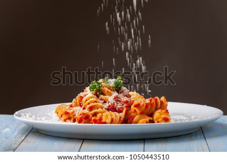 parmesan cheese falling on pasta