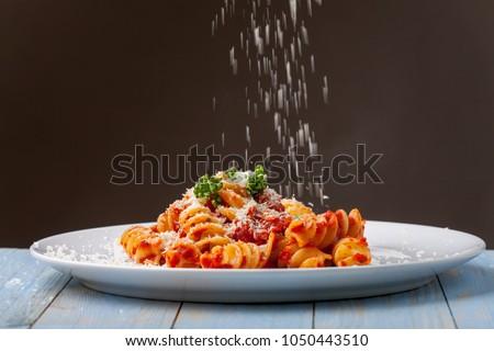 parmesan cheese falling on pasta