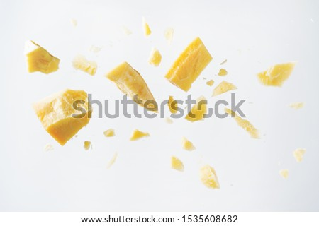 Parmesan cheese flying in different directions with crumbs on a white background with space for the text.