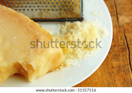 Parmesan cheese freshly grated on a white plate with wood background.