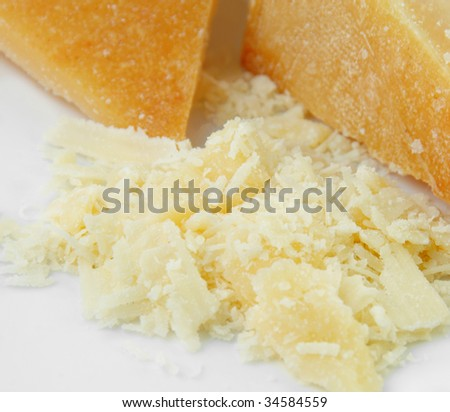 Parmesan cheese freshly grated on white plate.
