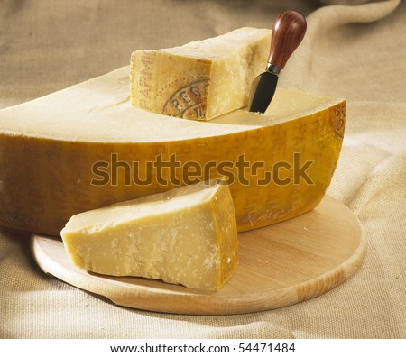 parmesan cheese on a wooden table with knife