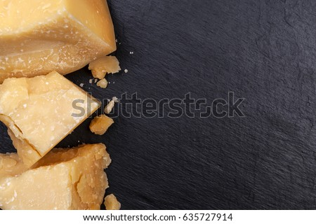 Parmesan cheese on black stone background. Top view, copy space.