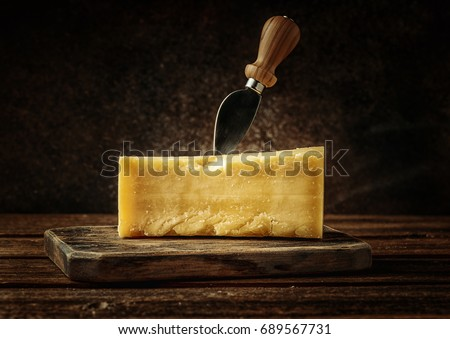 Parmesan cheese on rustic wooden board.