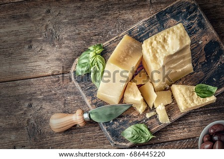 Parmesan cheese on wooden board with basil leaves. Top view.