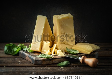 Parmesan cheese on wooden board with basil leaves. Vintage view.