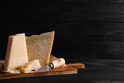 Parmesan cheese with board and knife on black wooden table. Space for text