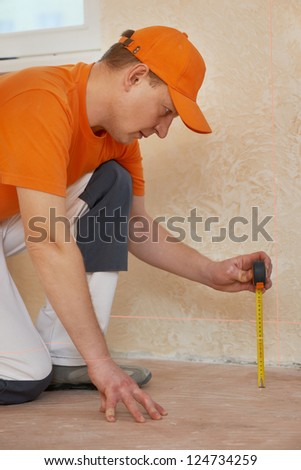 parquet carpenter worker use laser beam level to determine floor problem before installing wood board during flooring work - stock photo