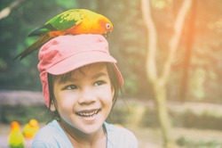 Parrot is eating food on little girl head.