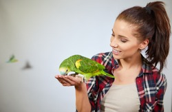 parrot sitting on a girls hand and kissing her .