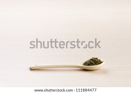 Parsley in a spoon over a blurred wooden background with copy space