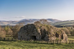 Parson's Tower ruin now a listed building close to Ford Castle seen in warm early evening light with clear blue sky, open borderland countryside and The Cheviot mountain in the background