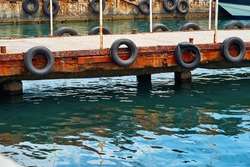 part closeup of old concrete sea berth or pier with car tires for mooring boats and yachts