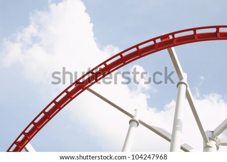 Part curve of red and white roller coaster rail.