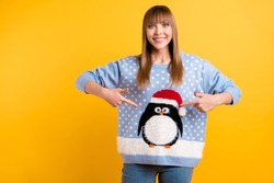 Part in ugly sweater party event concept. Photo of cheerful teen lady demonstrating pattern with comic cute sweet lovely animal in santa claus cap on outfit isolated bright color background