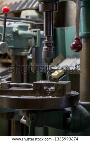 Part machining with drilling machine #1335993674