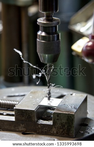 Part machining with drilling machine #1335993698