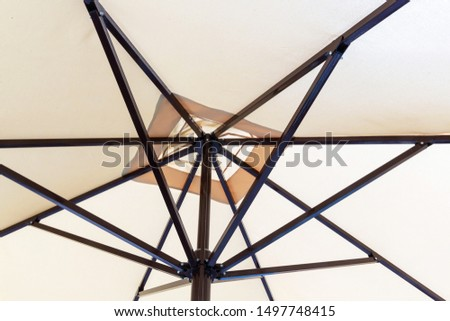 Part of a beach, beige, cloth umbrella with a steel, black mechanism. Background image. #1497748415