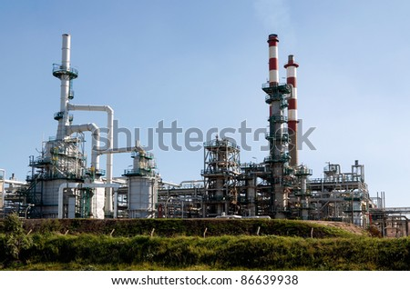 Part of a big oil refinery against blue sky showing some new equipment