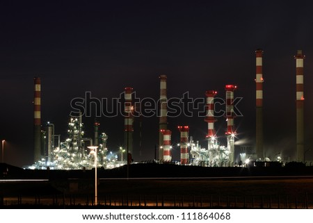 Part of a big oil refinery and power-plant by night - stock photo