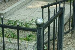 part of a black  metal decorative fence made of iron bars at the grave in the cemetery