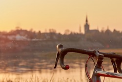 Part of a black red gray racing bike on the river in the yellow orange evening light at sunset in front of the skyline, insects fly through the picture