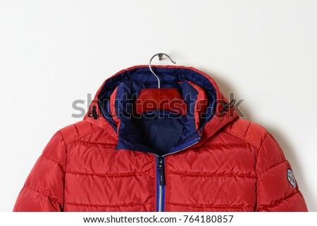 Part of a bright red jacket is a down jacket with a hood and an unbuttoned collar. Winter outerwear for men. Close-up. - Shutterstock ID 764180857