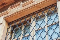 Part of a Christian church window made of wood with a metal grill. New wooden building in Russian style.