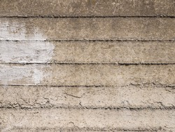Part of a concrete surface with rough joints and stains of white paint.