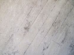 Part of a concrete wall with diagonal formwork joints. Rough surface with wood panel texture.