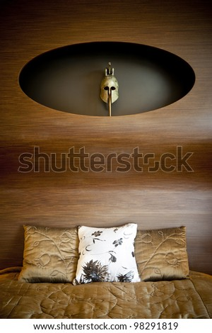 Part of a design bedroom with an ancient greek mask and pillows.