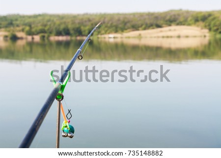 Part of a fishing rod on water background. Selective focus #735148882