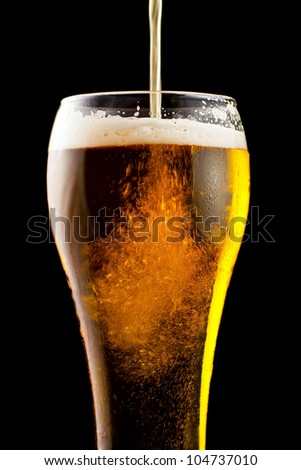Part of a glass of cold beer is a light froth.