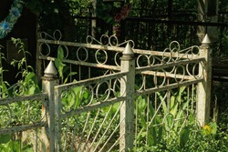 part of a gray old metal decorative fence made of iron bars overgrown with green grass at the grave in the cemetery
