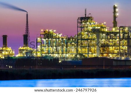 Part of a heavy Industrial Chemical area with vibrant surreal mystical colors and lights in twilight